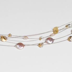 Zarte Halskette mit Perlen und silbernen und vergoldeten Plättchen.