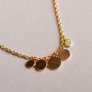 Zarte vergoldete Silberkette 'Five Coins' . Die 5 verschieden großen Plättchens sind aus 925 Silber oder Silber vergoldet. Die dezente Kette hat ein Verlängerungskettchen von ca. 10 cm und passt so mühelos bei ganz verschiedenen Trägerinnen. Passt hervorragend zum gleichnamigen Armband.