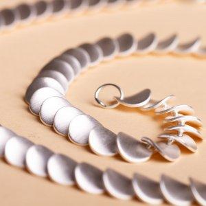 Silbercollier mit gewellten Plättchen. Diese Kette legt sich superschön um den Hals der Trägerin und erinnert ein wenig einen Halsreifen aus Silber – nur anschmiegsam.