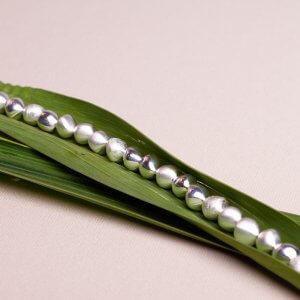 Collier aus tropfenförmigen Silberkugeln. Die einzelnen Elemente haben verschiedene Oberflächen. Feinmatt, eismatt und poliert ergeben ein spannendes Gesamtbild. Schöne Alternative zur klassischen Perlenkette. Die Silberelemente haben einen Durchmesser von ca. 10mm. 925 Silber