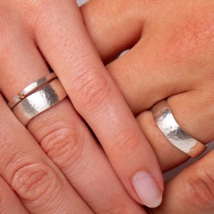"""Trauringe mal anders. Silber mit Hammerschlag und einer unegalen Kante. Sie trägt einen kleinen minimalistischen Ring mit einem kleinen """"Rotgoldknubbel"""" dazu. Wir mögen schlichte zeitlose Trauringe die euch ein Leben lang begleiten und wenn es etwas Abwechslung sein darf, dann steckt ihr immer mal einen anderen Ring dazu."""