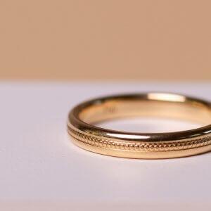 Trauring 18 Karat Gold verziert mit kleinen Kügelchen. Vielleicht mag es der/die Eine verspielt und der/die Andere ganz schlicht? Warum nicht! Hauptsache, die Ringe gefallen nach der Hochzeit, ihr mögt sie gern tragen und sie werden für euch zu einem steten und gern gesehenen Begleiter.