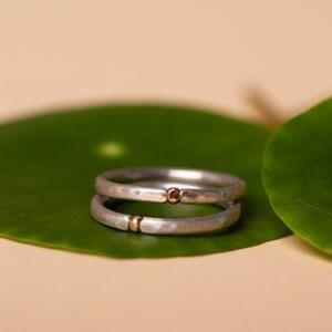 Minimalistisch und günstig – wir finden auch das dürfen eure Eheringe sein. Hier z.B. 925 Silber mit Hammerschlag und einem kleinen 14 Karat Rotgoldelement. Stückpreis bei individueller Anfertigung ab 149 €