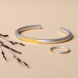 """Minimalistische Kombination """"Goldstück"""" aus unserem handgefertigten Armreif aus Silber mit dem passenden Silberring. Beide haben ein massives Goldplättchen aus 900er Gold aufgebracht."""