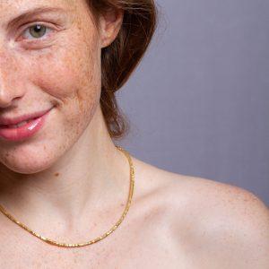 Ganz kleine quadratische Scheiben aneinandergereiht und auf einem Edelstahlseil aufgezogen ergeben eine feine Halskette in Gold die passend ist für jede Gelegenheit.