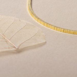Halskette Quadrat. Quadratische Scheiben auf einem Edelstahlseil aufeinandergereiht. Gibt's in zwei Größen, in Silber und in Silber vergoldet.