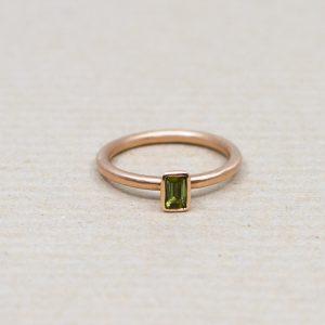 Der dunkelgrüne Turmalin ist geschliffen wie ein Smaragd und glitzert im Licht. Der Ring besteht aus 585 Rotgold ist mattiert.